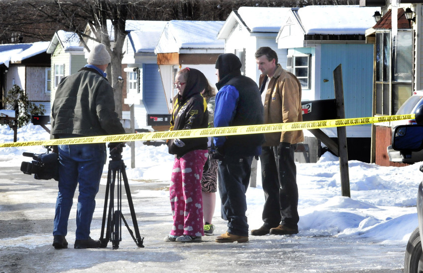 People gather behind police tape that cordoned off the scene of a mobile home fire on Pooler Parkway in Waterville's South End that killed David Chamberlain Monday morning.