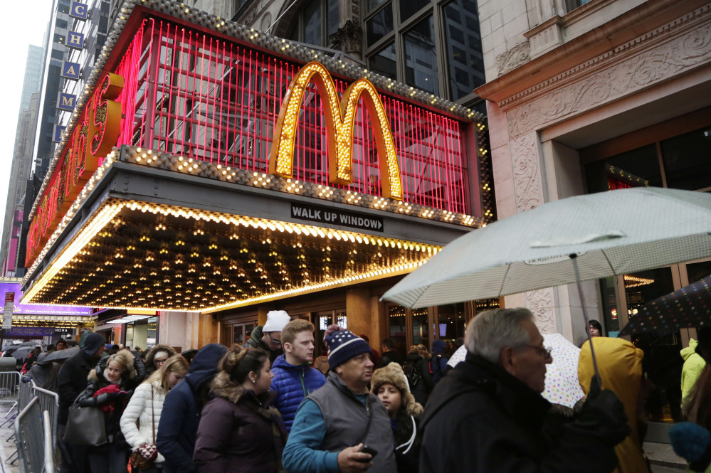 In this Tuesday, Dec. 29, 2015, photo, pedestrians pass under a McDonald's marquee in New York. McDonald's reports quarterly financial results, Monday.