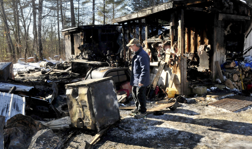 Maurice Bowring on Monday looks over the dryer that investigators determined was the source of fire that destroyed his home in Norridgewock last week.