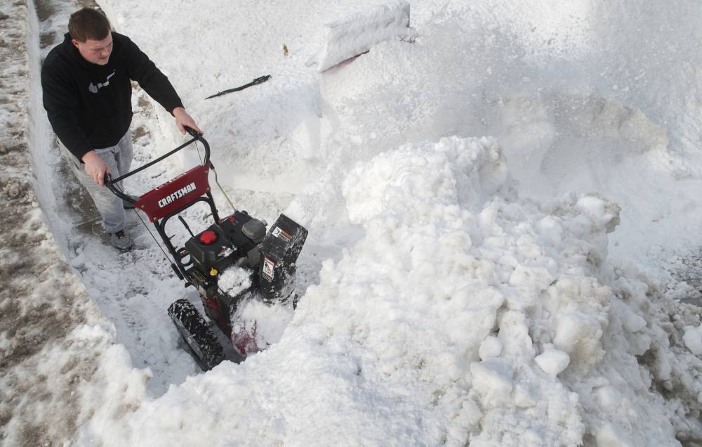 Dakota Barlow clears snow from the sidewalk in front of G&G Pizzeria in Somerdale, N.J., Monday.