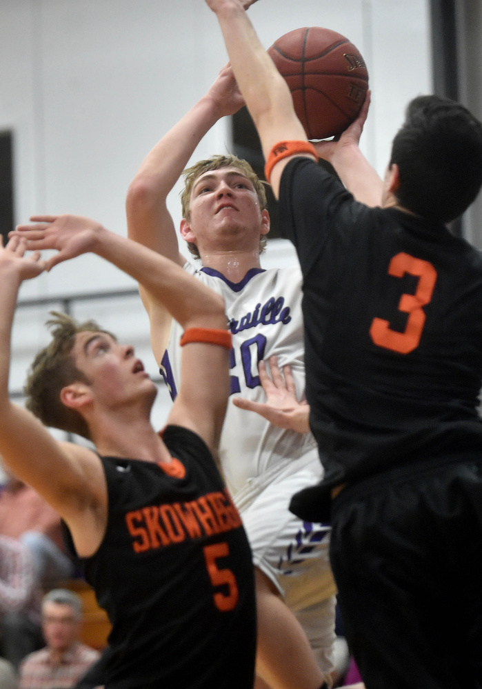 Waterville's Adam Barre, middle, takes a shot over Skowhegan defenders Issac Witham, left, and Cameron Barnes during a Kennebec Valley Athletic Conference Class A game Tuesday night in Waterville.