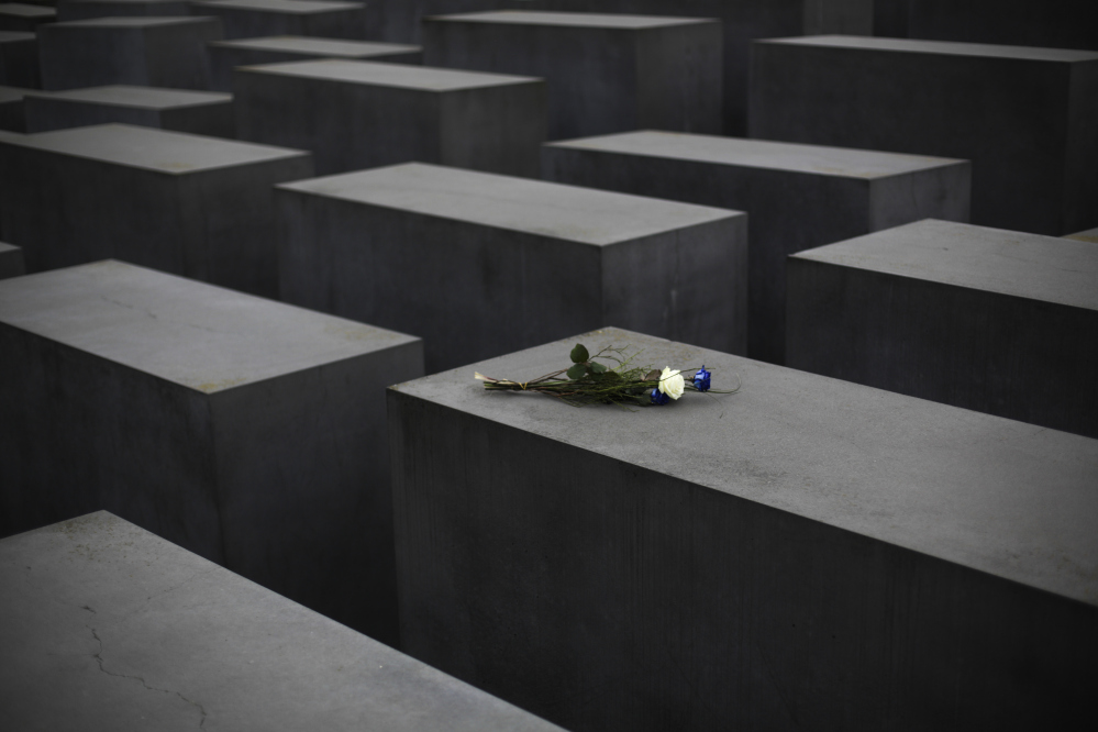 Flowers lay on a slab of the Holocaust Memorial to commemorate the victims of the Nazi regime at the International Holocaust Remembrance Day in Berlin, Wednesday.