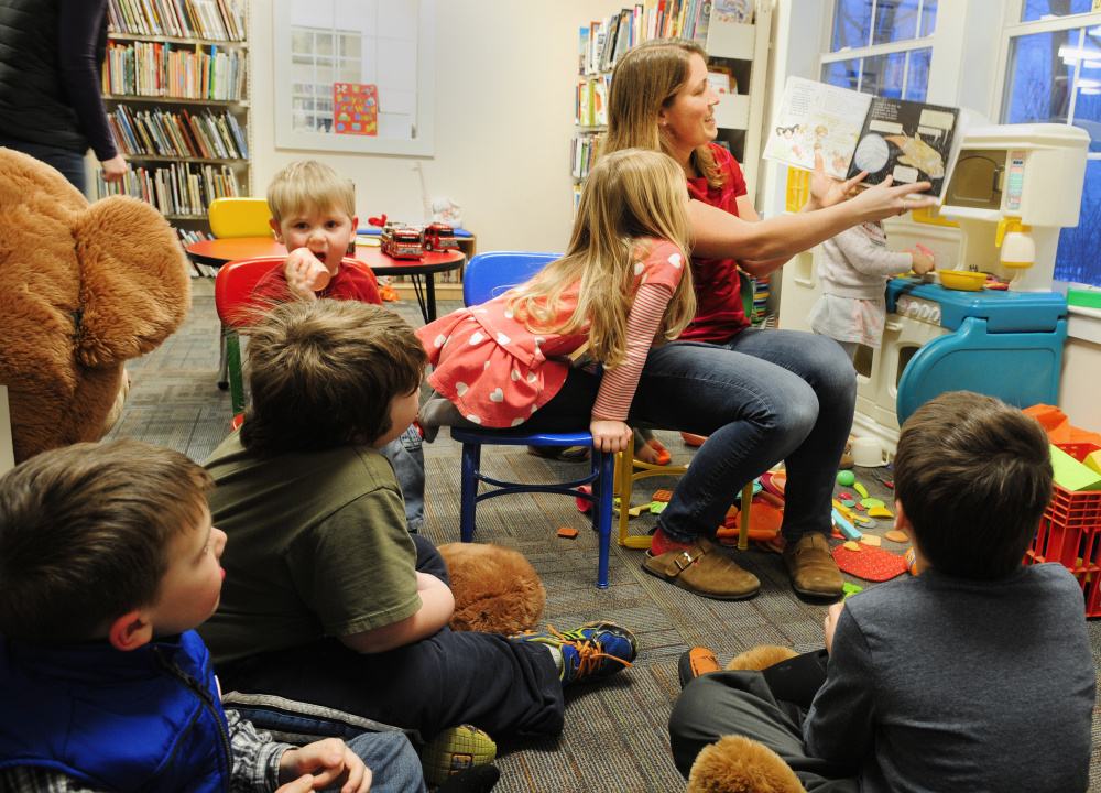 Volunteer Missy Dore reads to children during story hour on Tuesday at Umberhine Library in Richmond. Dore organized the GoFundMe page to raise money after a recent robbery at the Richmond library.