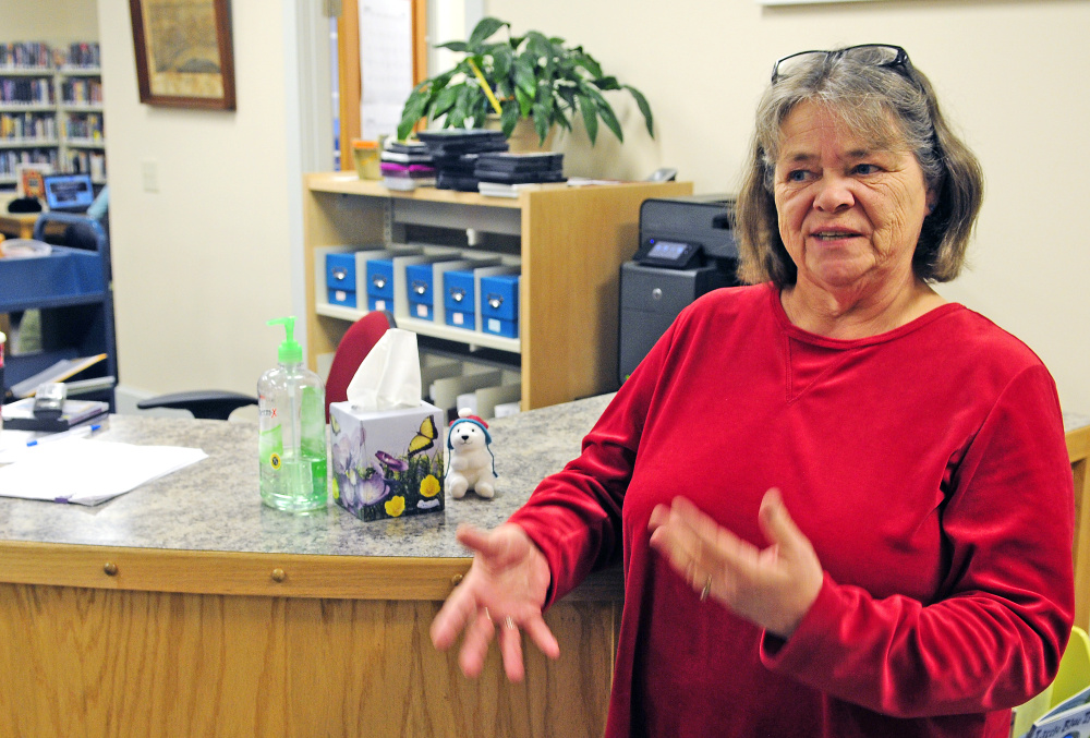 Librarian Donna McCluskey talks Tuesday about the donation jar that had been taken from the counter in a recent robbery at the Isaac F. Umberhine Public Library in Richmond.