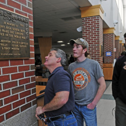 Machine tools instructor Darryl Nadeau, left, looks at the World War I memorial plaque that two of his students Colt Seigars and Mathew Musselman (cq) made brackets for on Tuesday in the Cony High School food court.