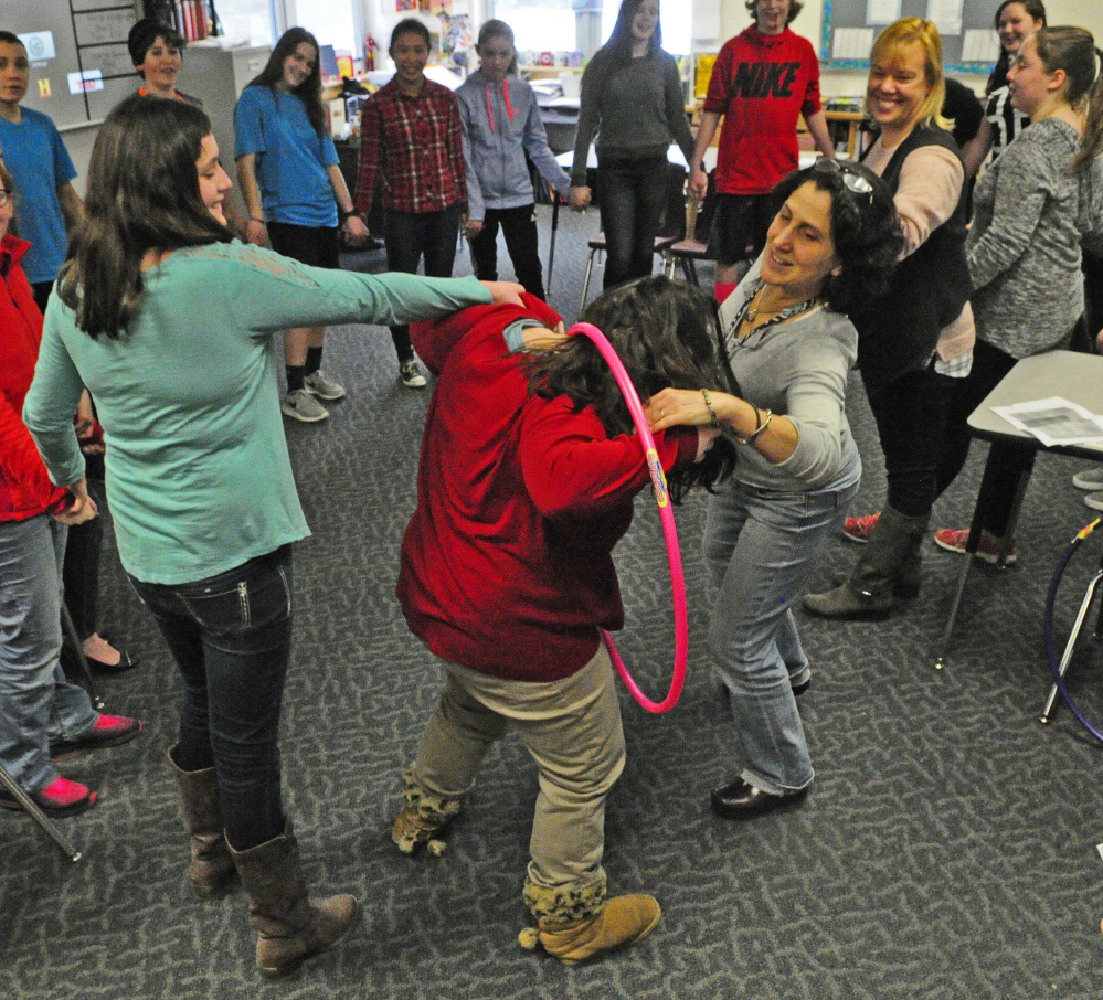 Students and staff participate in an activity where they had to move a hula hoop around the circle while still holding hands during Healthy Decisions Day events on Friday at Maranacook Community Middle School in Readfield.