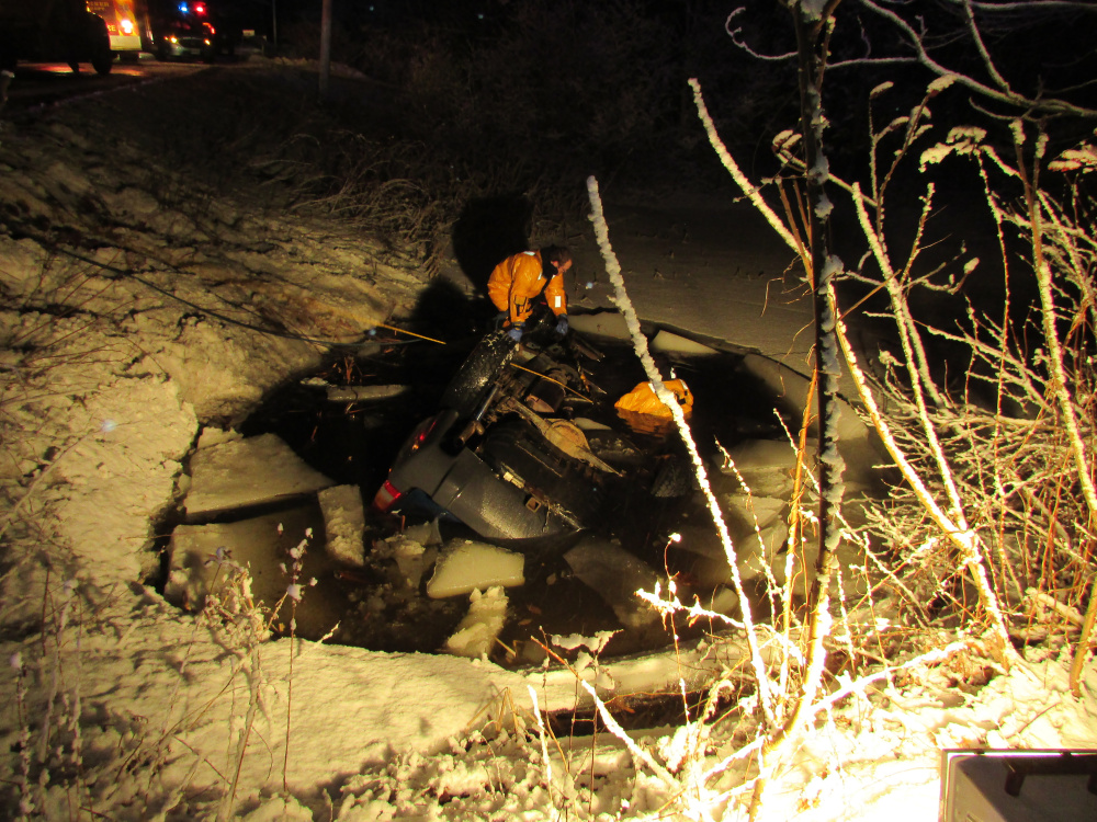 Members of the Gardiner Fire Department prepare to remove a 2003 Jeep from a pond Friday night after a crash that left a Woolwich man dead when his vehicle went off Route 27, rolled over into the pond and crashed on its roof through the ice.