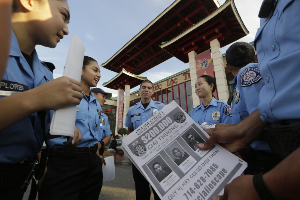 """Westminster teenage police volunteers fan out along the strip of Vietnamese restaurants and shops known as """"Little Saigon"""" to tell storekeepers about the escaped inmates and urge them to post fliers with their pictures to spread the word in Westminster, Calif."""