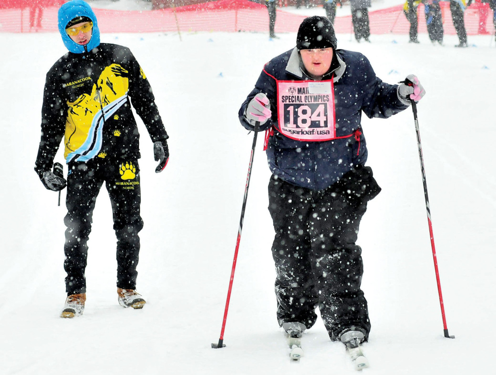 Caitlin Killarney, of Families Matter Inc., in Waterville, competes in 2014 in the 100-meter Nordic race during the 45th annual Special Olympics Maine Winter Games at Sugarloaf USA. At left, Colby Watts, of Maranacook High School cheers her on. This year's Special Olympics begin Sunday.