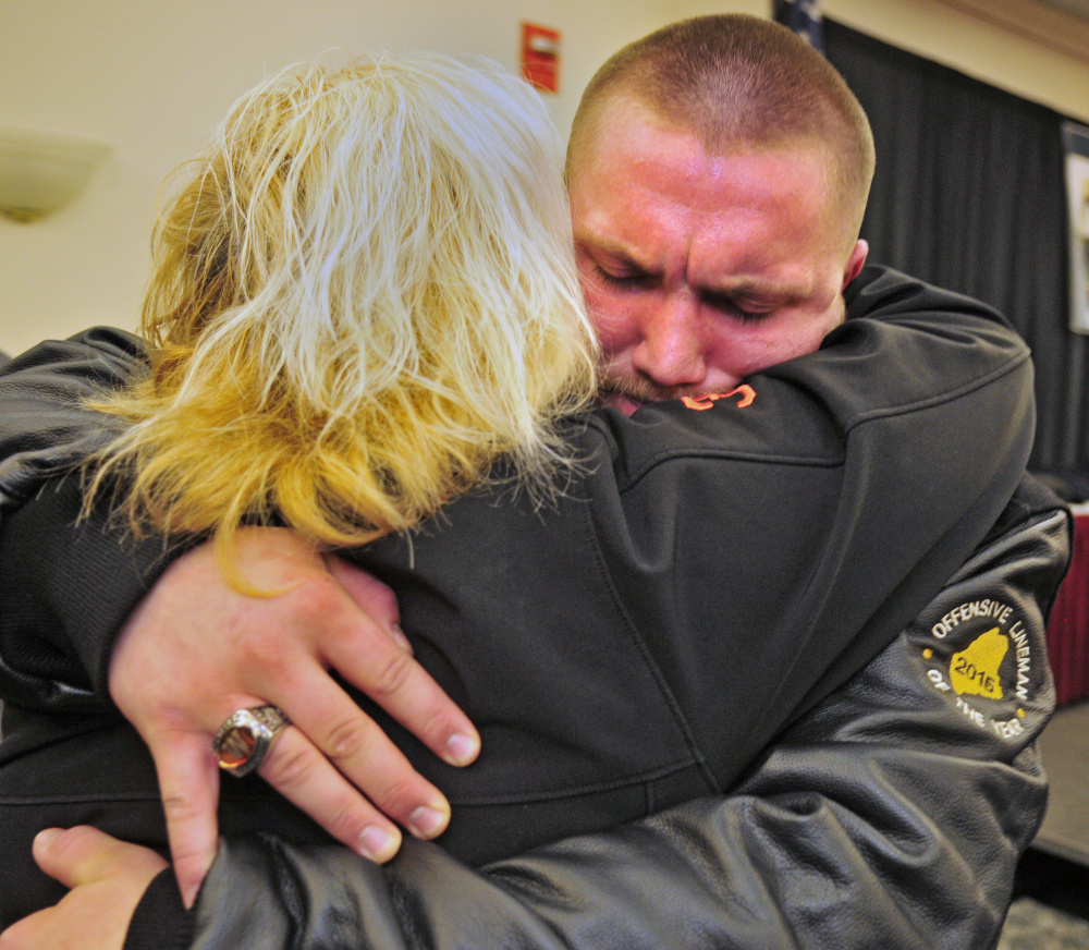Terri Clark, left, hugs her son, Winslow High School senior Alec Clark, after he won the Frank J. Gaziano Offensive Lineman Award on Saturday at the Augusta Civic Center.