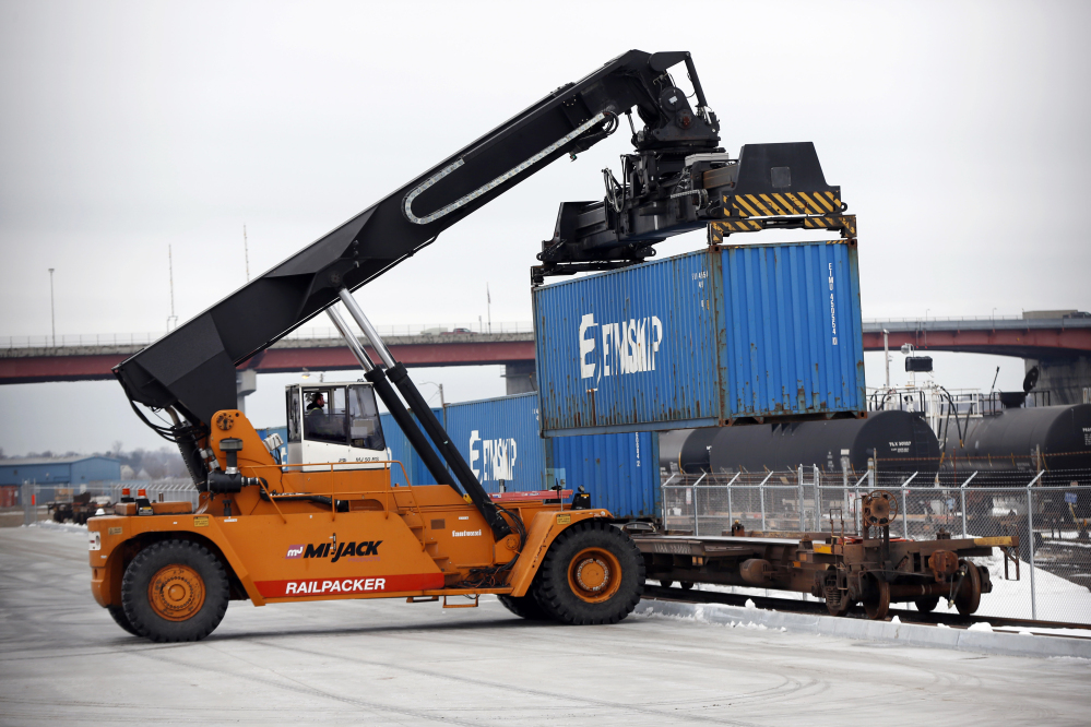 A reach stacker loads a train car with a container of Poland Spring Water on the waterfront in Portland. Freight trains are rolling through New England carrying the first-ever shipping containers loaded on the Portland waterfront.