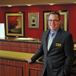 General Manager Alec Rogers stands in the lobby on Friday at the Quality Inn & Suites Maine Evergreen Hotel in Augusta, where he said security measures are a top priority for the safety of his staff and guests.