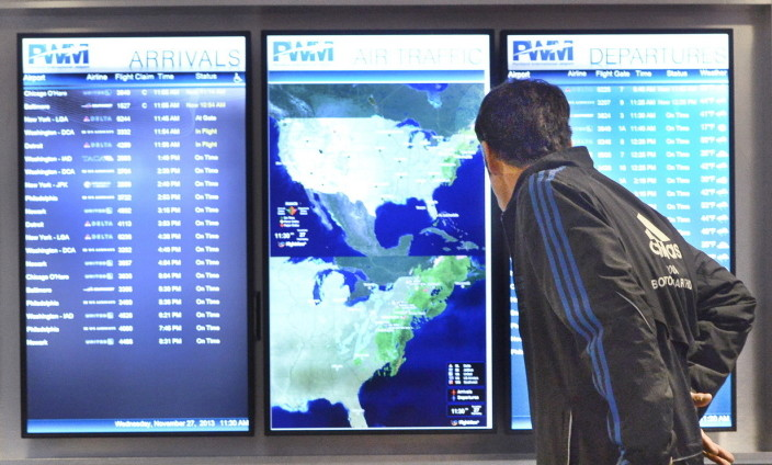 A passenger checks the flight schedule at the Portland International Jetport. Even if there is no snow in Maine, it's unlikely all flights will come and go as planned Friday and Saturday, particularly those that pass through Washington, D.C., and Baltimore.