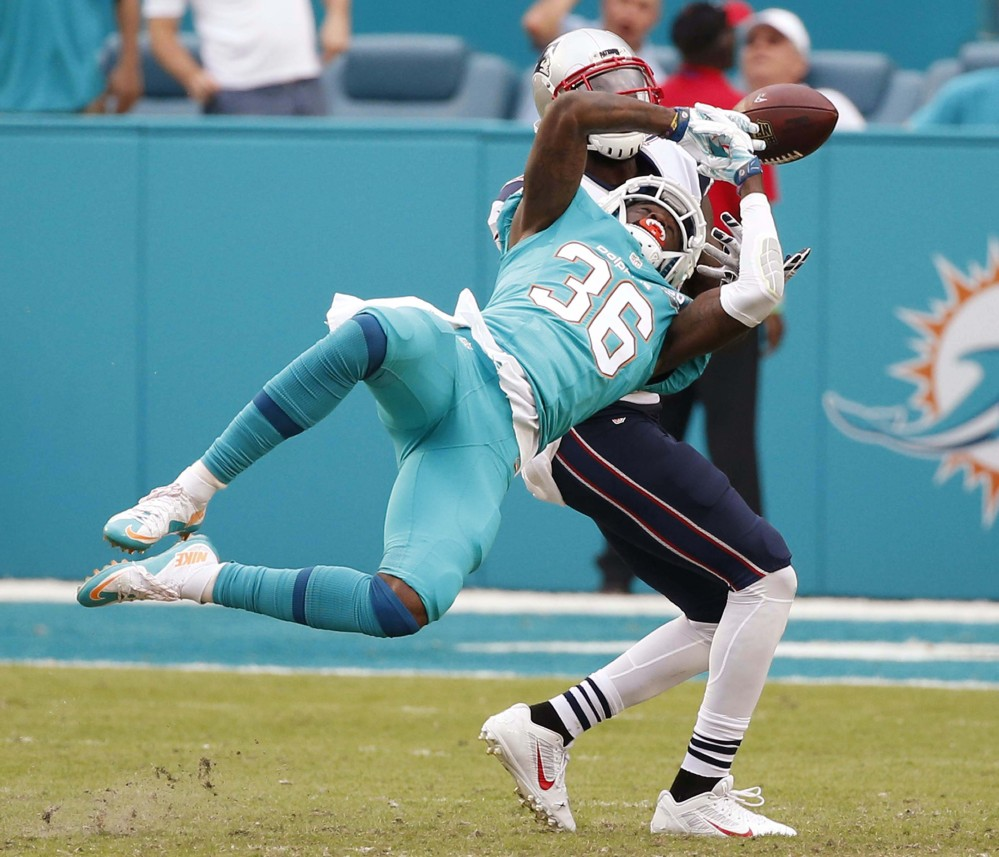 Miami Dolphins defensive back Tony Lippett attempts to intercept a pass intended for New England Patriots wide receiver Brandon LaFell in Sunday's game.