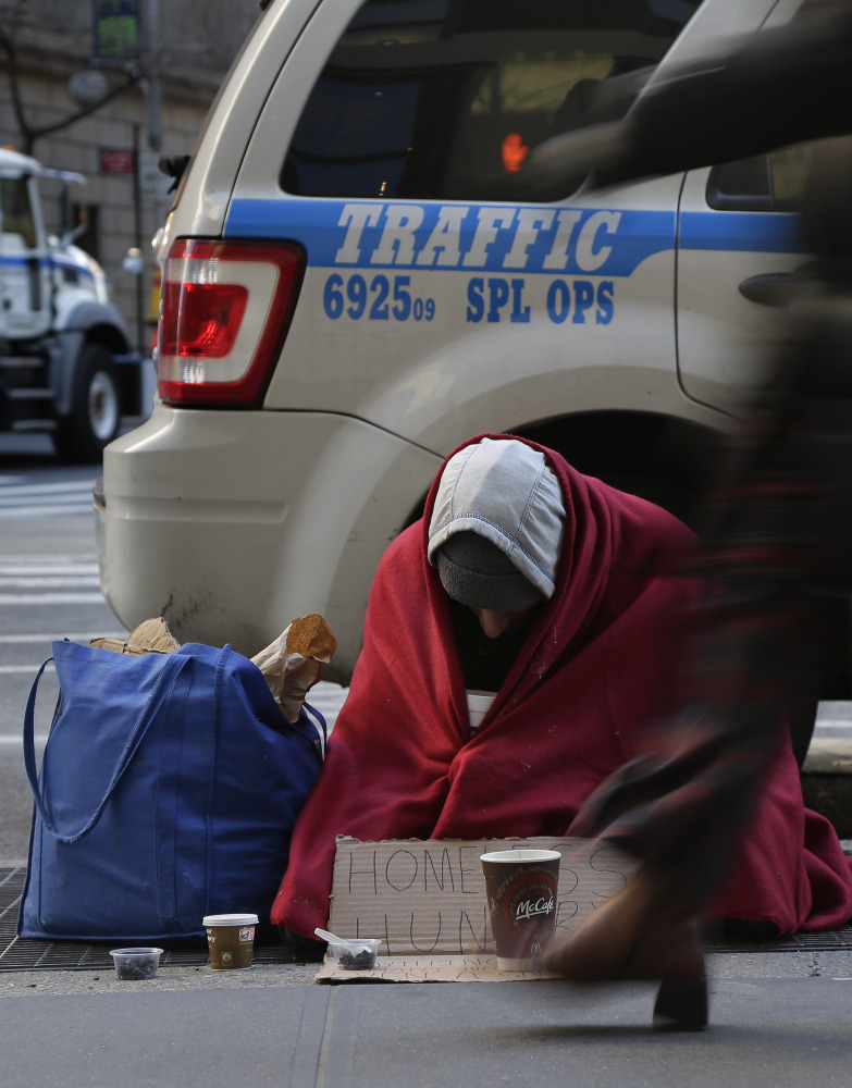Mike Lago, a homeless man, sits on a New York City sidewalk in freezing conditions Monday.