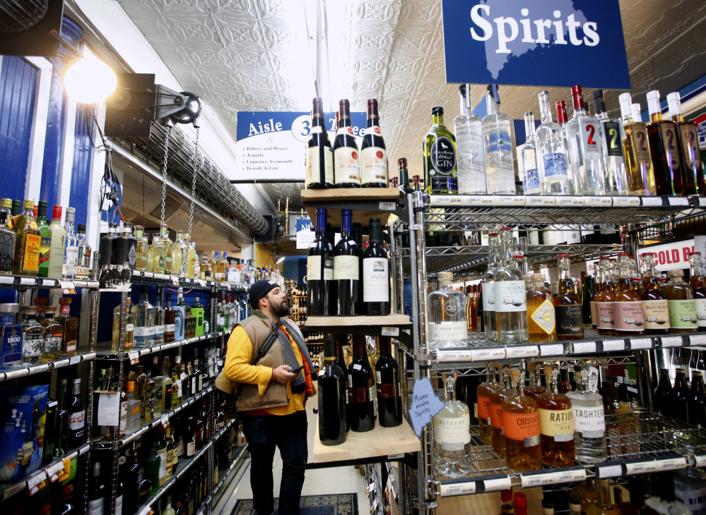 Ben Graham, 35, of Portland shops Monday at Maine Beer and Beverage Co. The new pricing system at state-run liquor stores will initially take an estimated $1.7 million from government coffers.