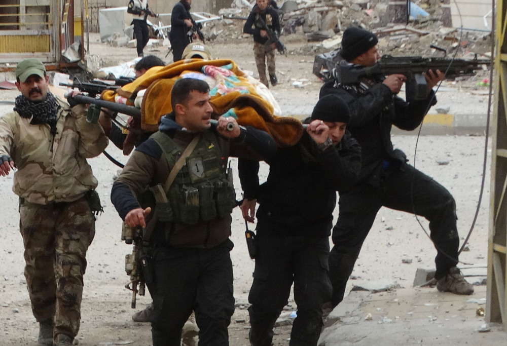 Iraqi security forces and allied Sunni tribal fighters evacuate a woman after she was shot by Islamic State extremists as she tried to cross neighborhoods in Ramadi during fighting Monday.