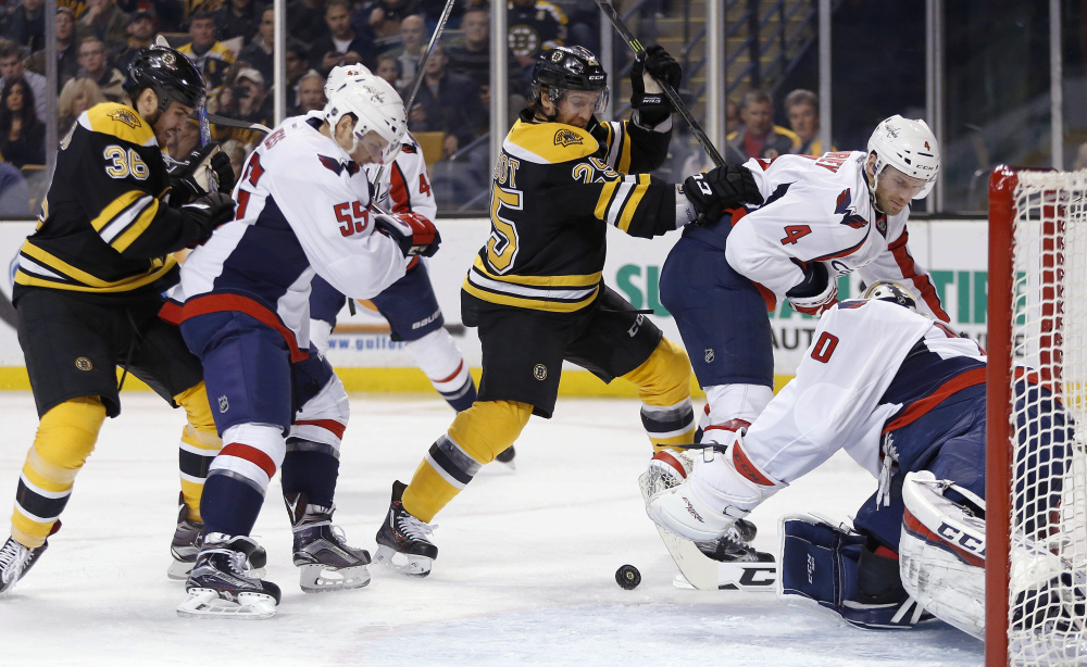 The Bruins' Max Talbot (25) battles the Capitals' Aaron Ness (55) for a rebound off goalie Braden Holtby during the second period Tuesday night. The Bruins came up short in a 3-2 home loss.