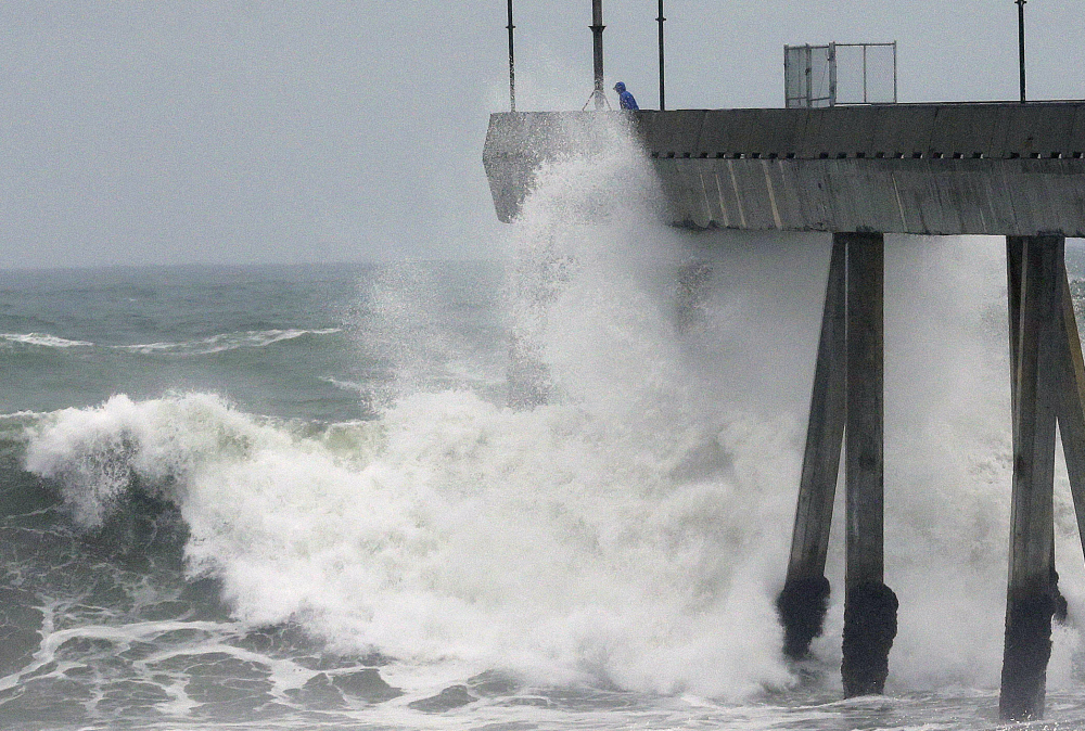 A man stands near crashing waves on the Pacifica Pier in Pacifica, Calif., Tuesday. El Nino storms lined up in the Pacific, promising to drench parts of the West for more than two weeks and increasing fears of mudslides and flash floods.
