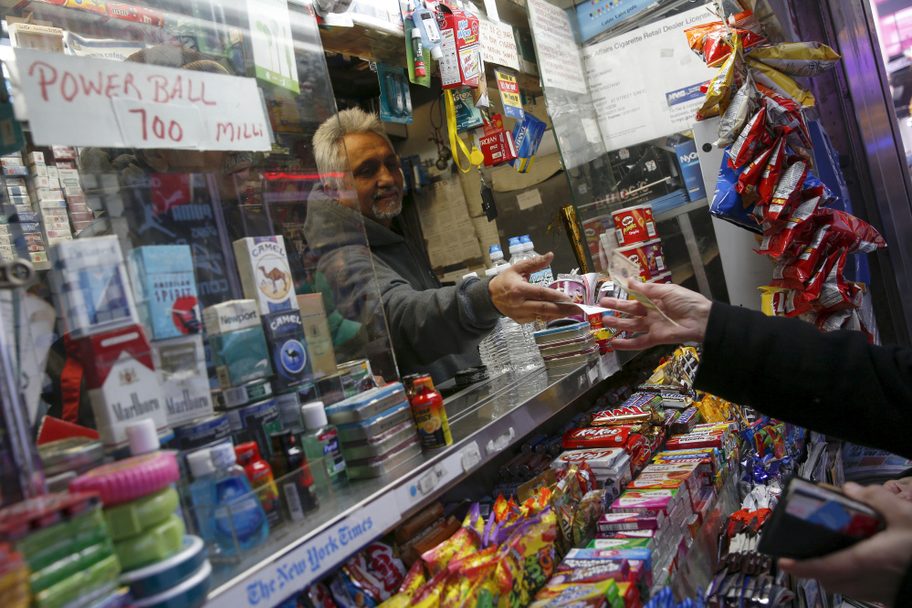 A vendor sells a ticket for the $700 million Powerball lottery draw at Times Square in New York on Thursday. The drawing will be held Saturday.