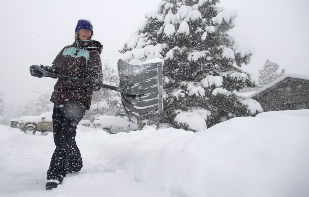 Jennifer Corrigan shovels snow in her driveway in Flagstaff, Ariz., on Thursday. El Nino-fueled storms also brought heavy snow to northern Arizona. Meteorologists say powerful climactic forces are at work this winter.