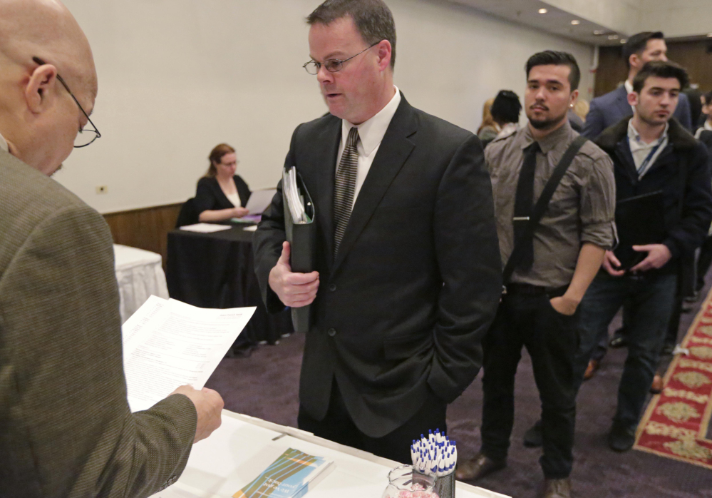 James Smith, center, leads a pack of job applicants at a National Career Fairs event in Chicago last April. U.S. employers added 2.65 million jobs in 2015, a monthly average of 221,000. It was the second-best year for hiring since 1999, after 2014.