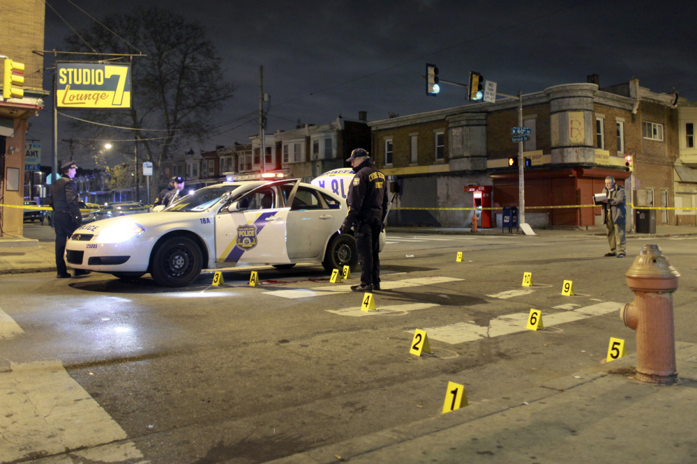 Officers investigate the scene of a shooting Friday in Philadelphia. A Philadelphia police officer was shot multiple times by a man who ambushed him as he sat in his marked police cruiser, authorities said.