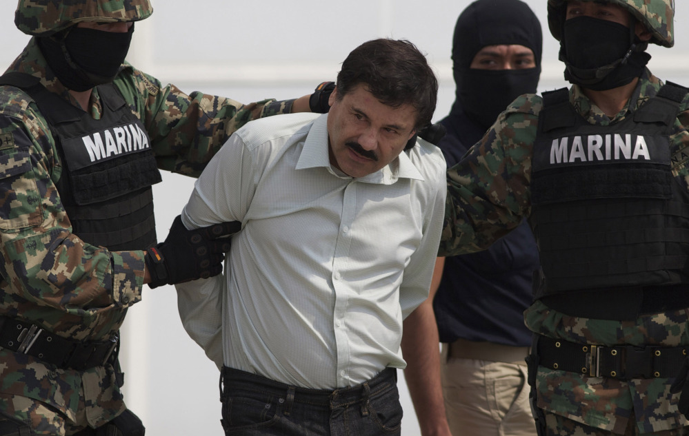 """Joaquin """"El Chapo"""" Guzman is escorted to a helicopter in handcuffs by Mexican navy marines at a hangar in Mexico City in 2014. Mexican President Enrique Pena Nieto posted on his Twitter account Friday that Guzman was recaptured."""