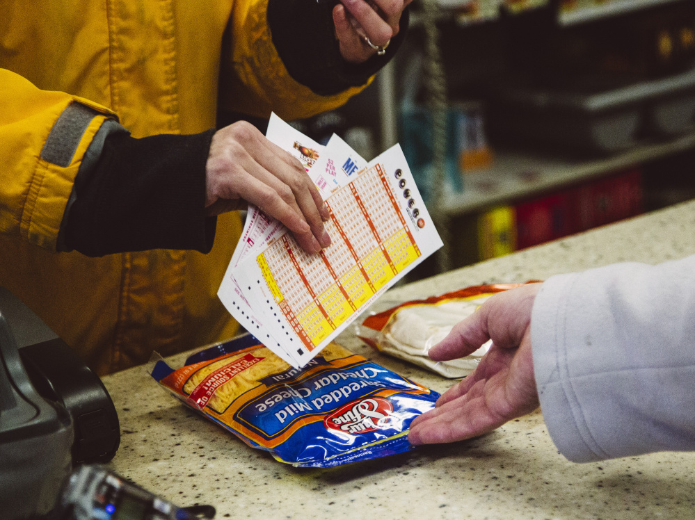Cashier Sabrina Meserve hands a Powerball ticket to a customer at Paul's Food Center in Portland on Thursday. Ticket sales soared after no one won the $700 million jackpot on Wednesday. The jackpot reached $800 million Friday, and could top $1 billion if no one wins Saturday, lottery officials say.
