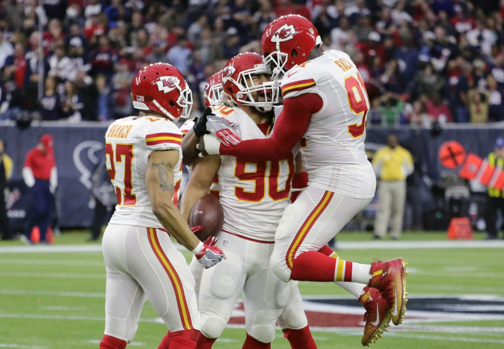 Kansas City Chiefs inside linebacker Josh Mauga, center, celebrates with teammates after he intercepted a pass thrown by Houston Texans quarterback Brian Hoyer during an wild-card playoff game Saturday in Houston.