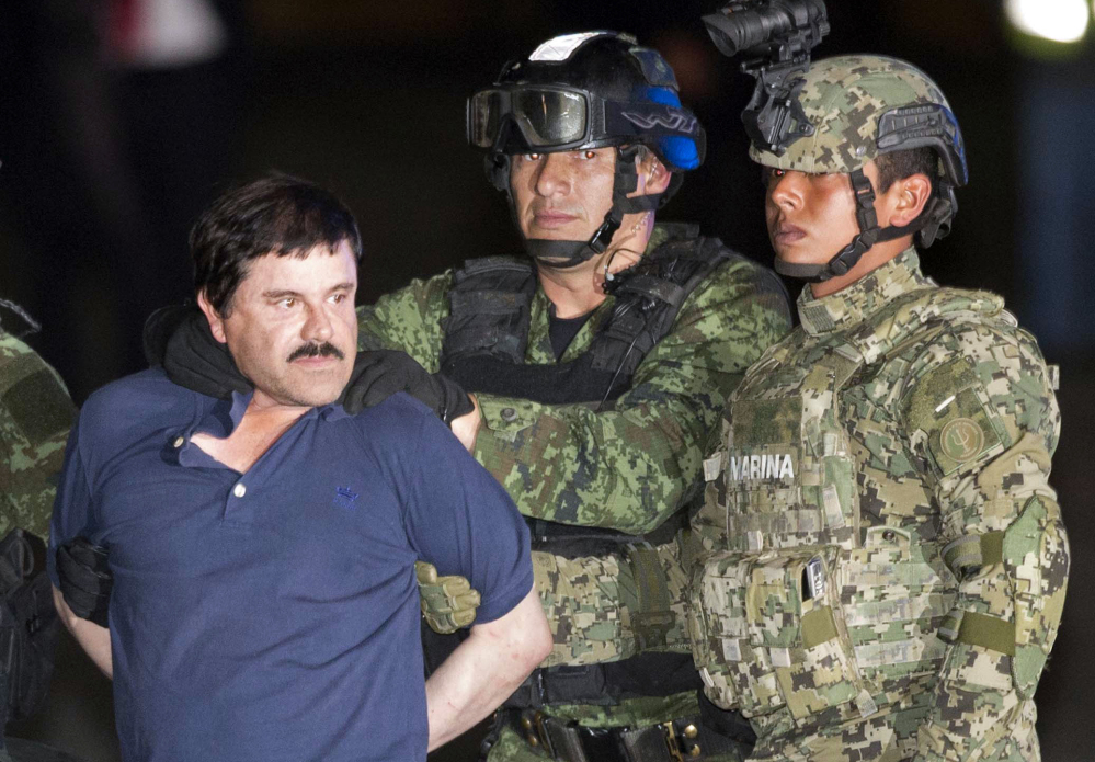 """Joaquin """"El Chapo"""" Guzman is made to face the press as he is escorted to a helicopter in handcuffs by Mexican soldiers and marines at a federal hangar in Mexico City, Mexico."""