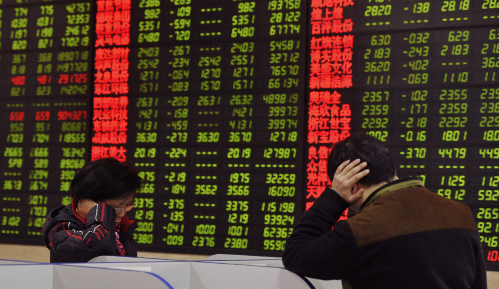 Investors check stock prices at a brokerage house in Fuyang, in China's Anhui province, Monday. China's stock benchmark sank more than 5 percent Monday.