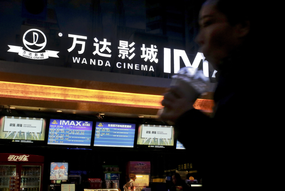 A Chinese moviegoer walks into the Wanda Cinema at the Wanda Group building in Beijing on Tuesday.