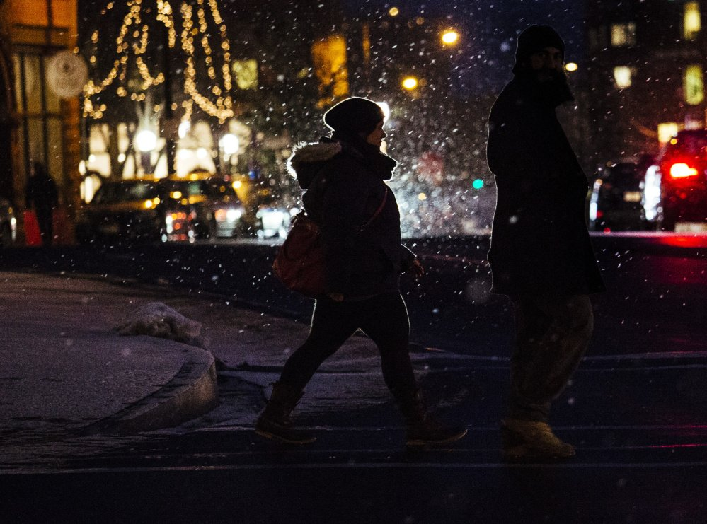 A pedestrian crosses Spring Street as snow billows around her in Portland on Tuesday.