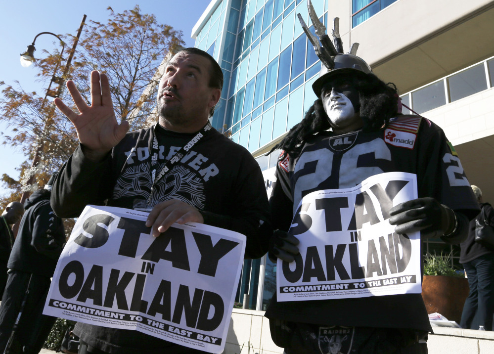 Oakland Raiders fans Griz Jones, left, and Ray Perez make their case for keeping the NFL football team in Oakland outside the Houston hotel where NFL owners were meeting Tuesday to discuss possible relocation to Los Angeles. (AP Photo/Pat Sullivan)