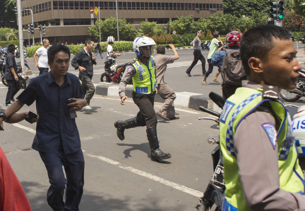 People, including unarmed police officers, flee from a gun battle that broke out following an explosion in Jakarta, Indonesia, on Thursday. The Associated Press