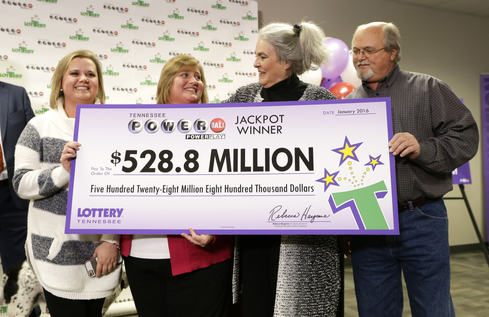 Rebecca Hargrove, second from right, president and CEO of the Tennessee Lottery, presents a ceremonial check to John Robinson, right; his wife, Lisa, second from left; and their daughter, Tiffany, left; after the Robinson's winning Powerball ticket was authenticated at the Tennessee Lottery headquarters Friday in Nashville, Tenn.