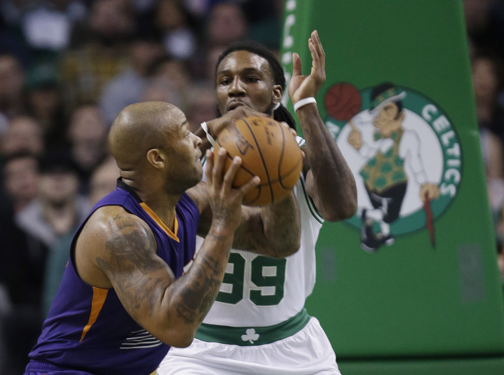 Suns forward P.J. Tucker takes the ball to the hoop against Celtics forward Jae Crowder in the first quarter of Boston's 117-103 win Friday night in Boston.