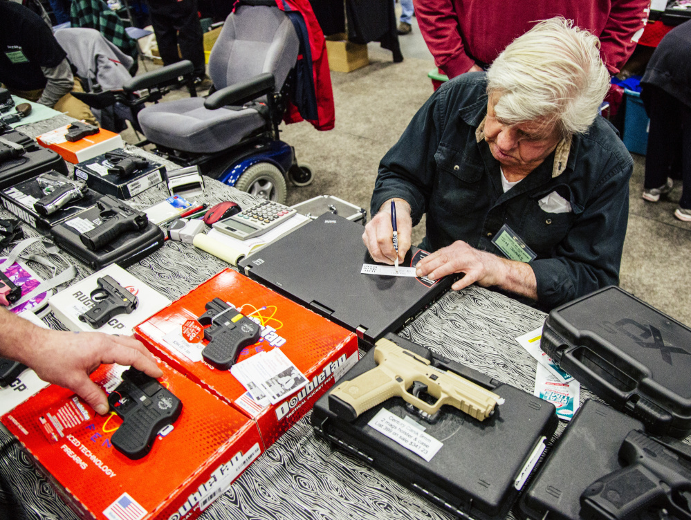 Jim Jones fills out a tag for a recently purchased handgun, while a customer fills out background check materials. Whitney Hayward/Staff Photographer