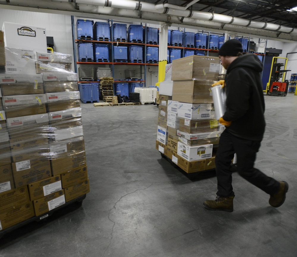 A worker wraps a pallet of food in plastic as he prepares to load a truck at Sysco food services in Westbrook. A federal study shows Mainers spend $3,736 a year on food, way above the U.S. average of $2,780.