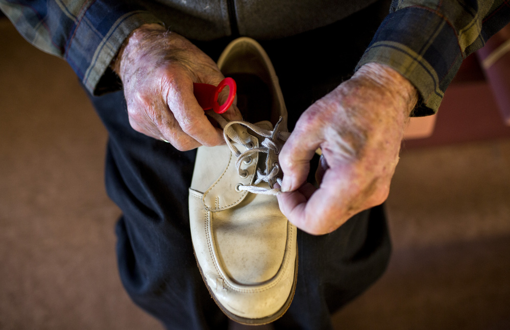 Vinton Lewis adjusts the laces of his bowling shoes before rolling a few frames at the Big 20 Bowling Lanes. Lewis has bowled off and on for about 50 years.