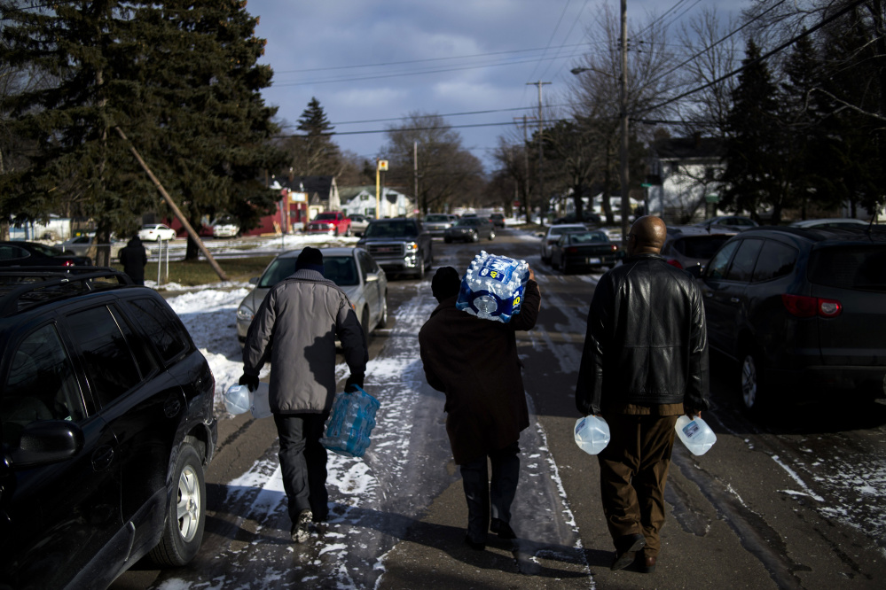 Flint residents Marcus Shelton, from left, Roland Young and Darius Martin walk on an ice-covered street as they retrieve free water Sunday at Heavenly Host Full Gospel Baptist Church in Flint, Mich. Flint's water became contaminated after Flint switched from the Detroit water system to the Flint River as a cost-cutting move.