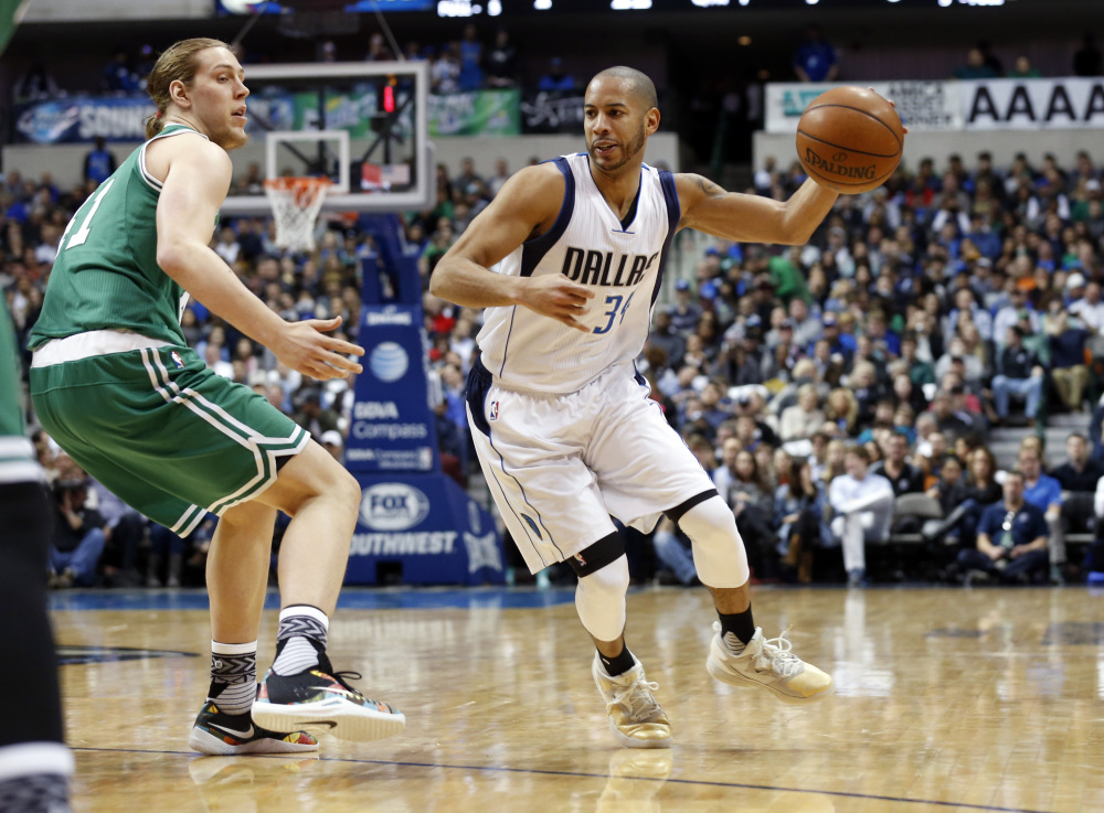 Celtics forward Kelly Olynyk defends against Dallas guard Devin Harris in the first half of a game that went to overtime, with the Mavericks winning after trailing by as many as six points in the fourth quarter.