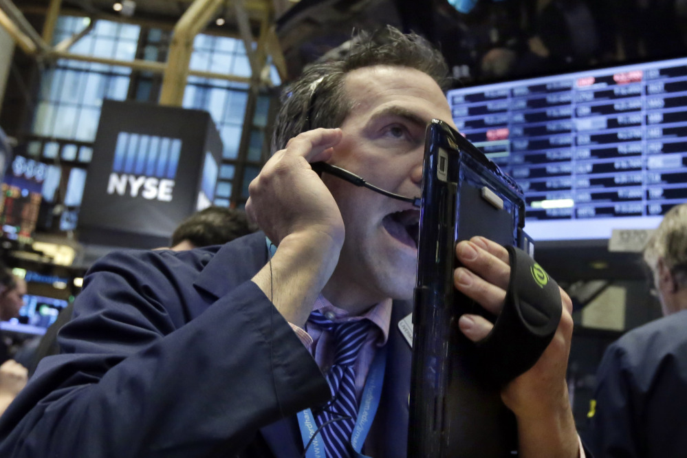 Trader Gregory Rowe works on the floor of the New York Stock Exchange on Wednesday, as energy stocks led another sell-off on Wall Street as the price of oil continued to plunge.