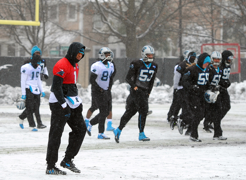 Carolina quarterback Cam Newton, left, and his teammates work out Friday on a practice field covered in snow and ice as they prepare for Sunday's NFC championship game.