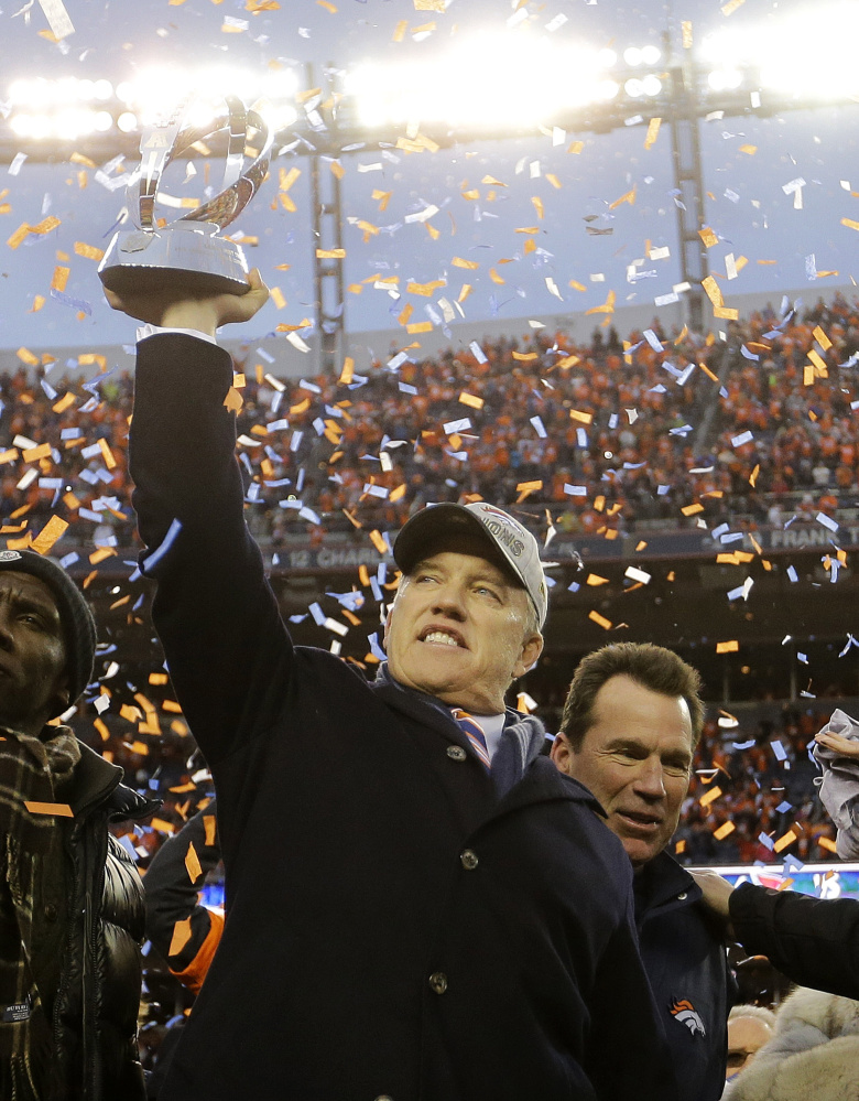 Denver Broncos general manager and executive vice president of football operations John Elway raises the AFC trophy following the AFC championship game.