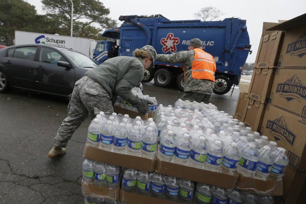 Members of the Michigan National Guard load bottled water at a fire station Thursday in Flint, Mich., where the municipal water supply is contaminated with lead.