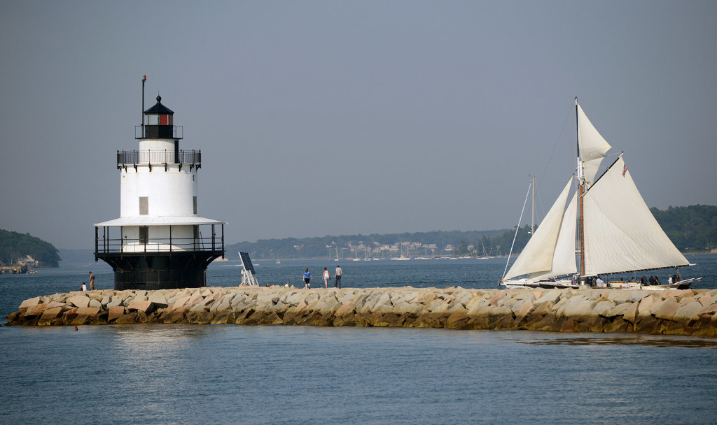 A sailboat navigates past Spring Point Ledge Lighthouse as visitors walk out on the breakwater in South Portland.