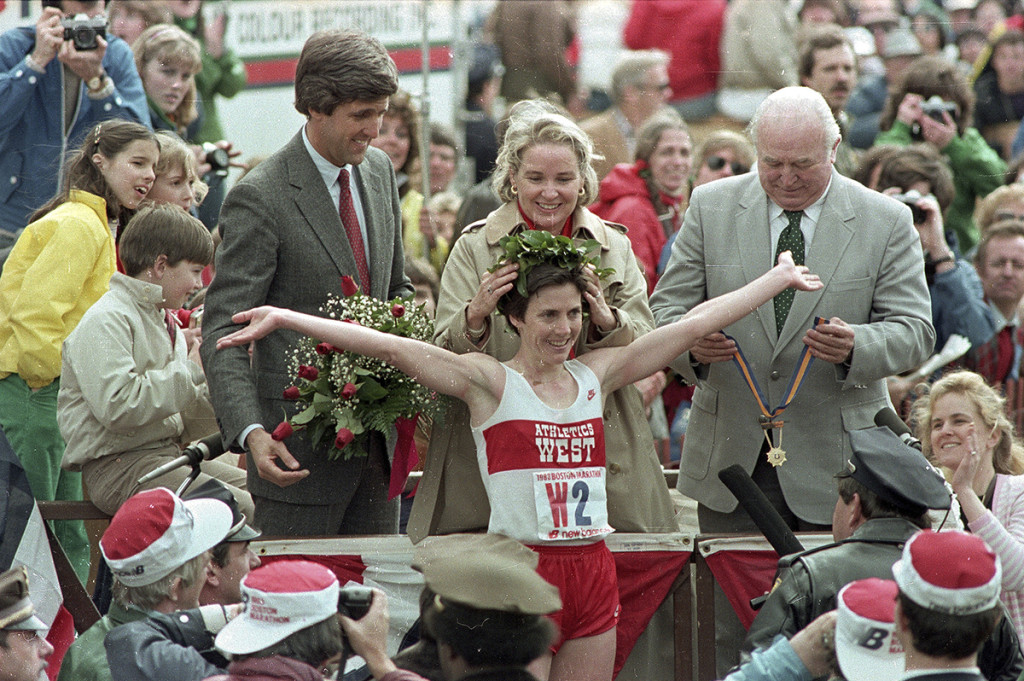 Joan Benoit receives her laurel wreath and reacts to cheering crowds after winning the Boston Marathon in record time for the women's division in this April 19, 1983,  photo. Then-Massachusetts Lt. Gov. John Kerry, in red tie, stands behind her. Benoit also won the women's division of the race in 1979. The Associated Press
