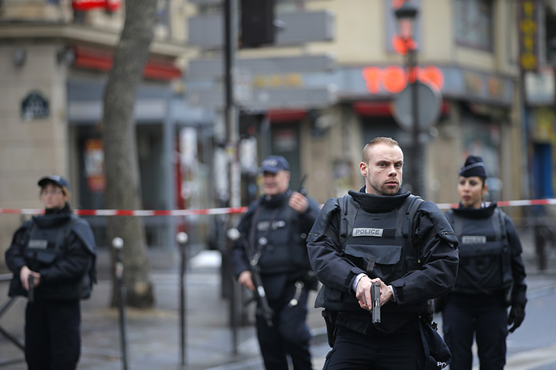 Police officers secure the perimeter near the scene of a fatal shooting which took place at a police station in Paris on  Wednesday. Two officials say the man had wires extending from his clothing and a knife.